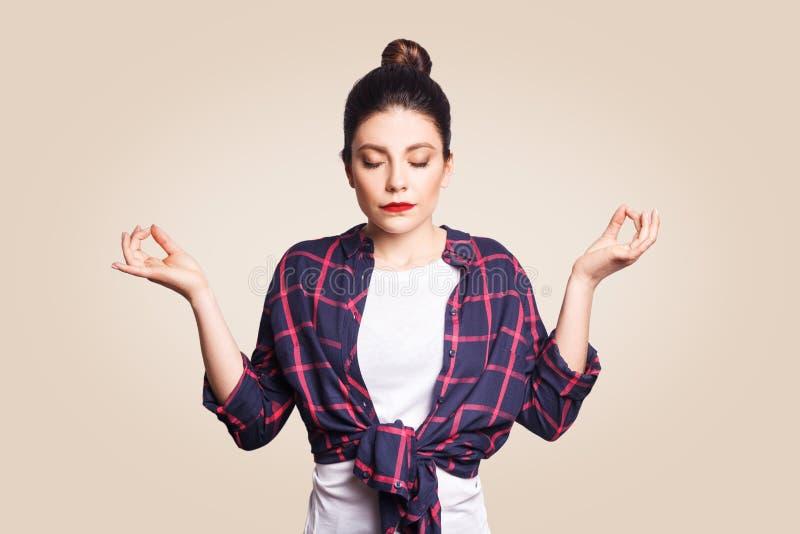 Раздумье, вероисповедание и духовность практикуют Красивая молодая девушка брюнет делая йогу в утре внутри помещения на бежевой с стоковые изображения