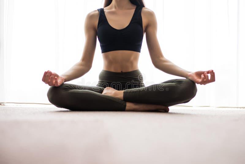 Раздумье йоги дома Ослабьте концепцию с непознаваемым духовным усаживанием молодой женщины Кавказская концентрируя модель Copyspa стоковые изображения rf