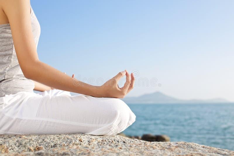 Раздумье молодой женщины в представлении йоги на тропический пляж стоковое фото