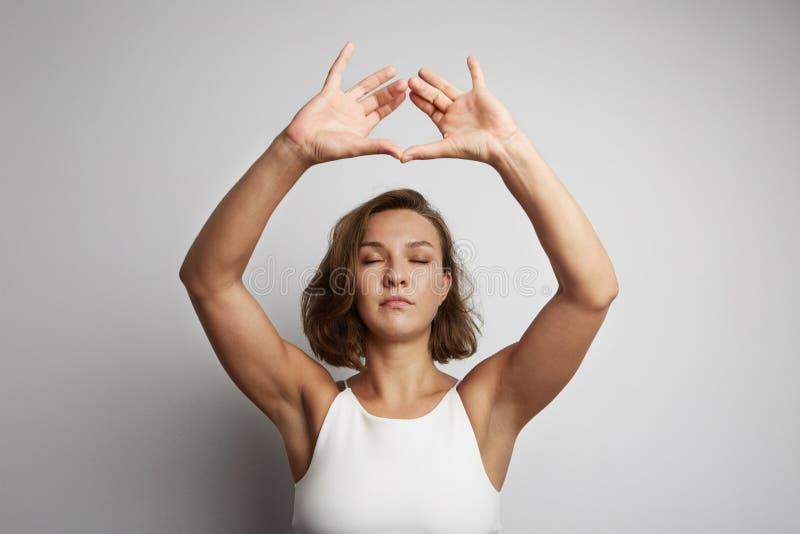 Раздумье на офисе, онлайн занятия йогой молодой женщины практикуя, принимая период отдыха на минута стоковое фото rf