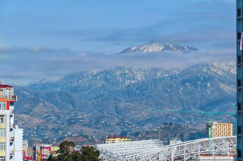 Район с природой в большом городке Холмы против фона города стоковая фотография