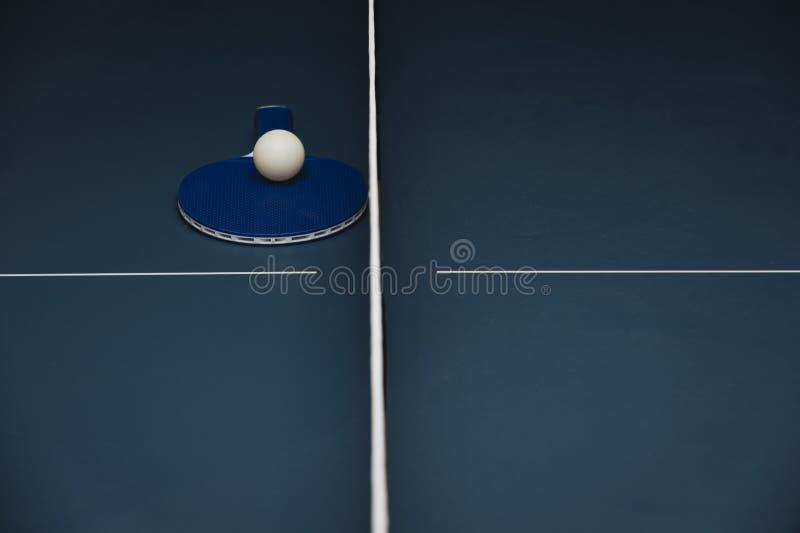 Ракетка, белый шарик и сеть на голубой таблице тенниса пингпонга стоковое изображение rf