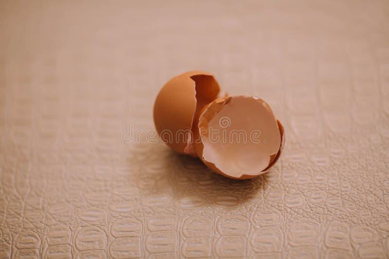 Раковина бежевого яйца, лежа на кухонном столе стоковое фото