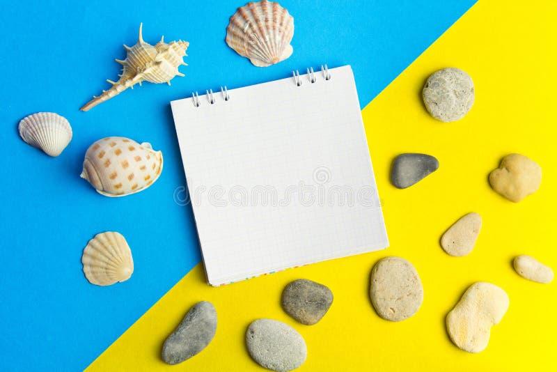 Раковины и камешки с компьтер-книжкой на голубом и желтом геометрическом pape стоковая фотография rf
