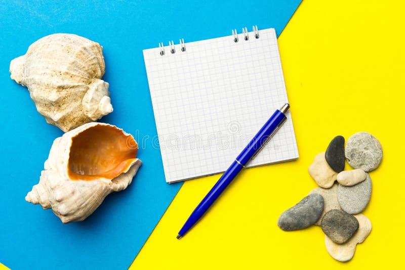 Раковины и камешки с компьтер-книжкой на голубом и желтом геометрическом pape стоковые изображения