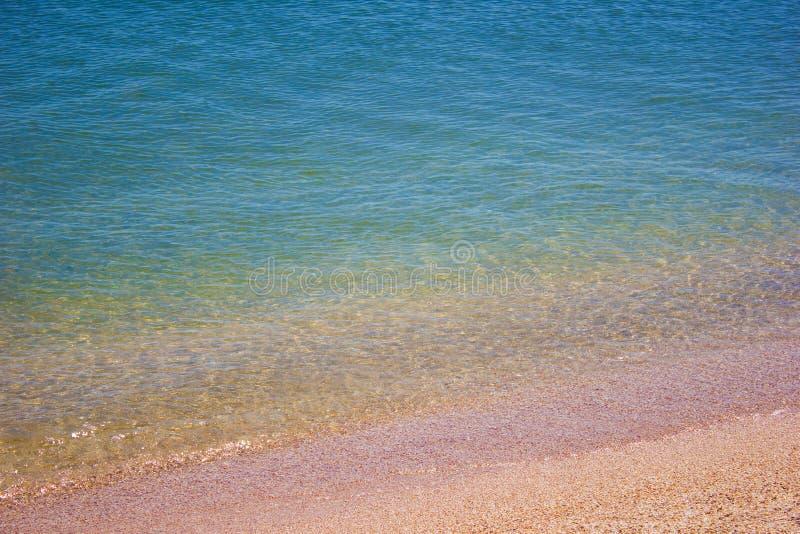 Раковины песка волны моря воды пляжа берега, текстура предпосылки стоковая фотография