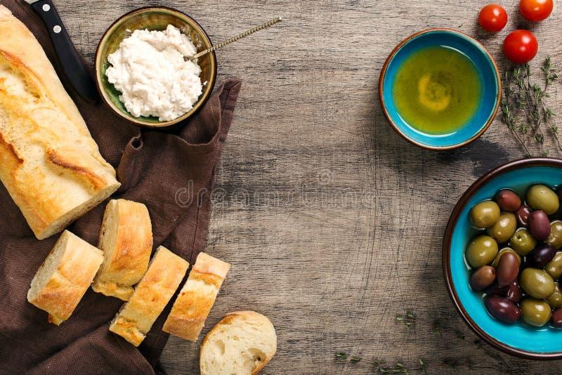 Рамка багета, масла, оливок, чеснока, трав, козий сыра, toma стоковые изображения rf