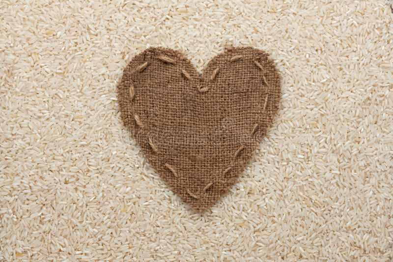 Рамка в форме сердца сделанного из мешковины с рисом стоковые фото