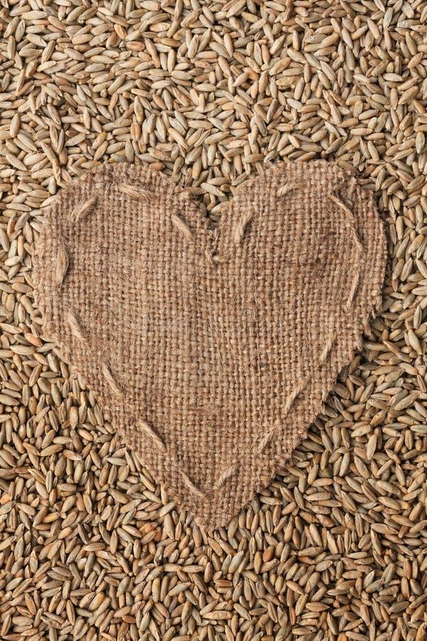 Рамка в форме сердца сделанного из мешковины с рожью стоковые фото