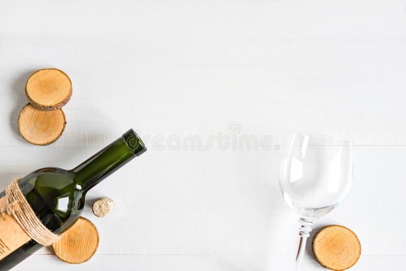 Рамка для знамени с бутылкой вина Бутылка с вином на белой деревянной предпосылке Праздничная предпосылка с местом для экземпляра стоковое изображение rf