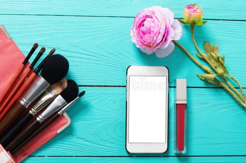 Рамка косметических продуктов и пустого передвижного экрана на голубой деревянной предпосылке Космос взгляд сверху и экземпляра д стоковая фотография rf
