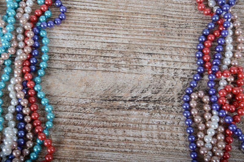 Рамка красочных бусин на текстурированном деревянном фоне стоковые фотографии rf