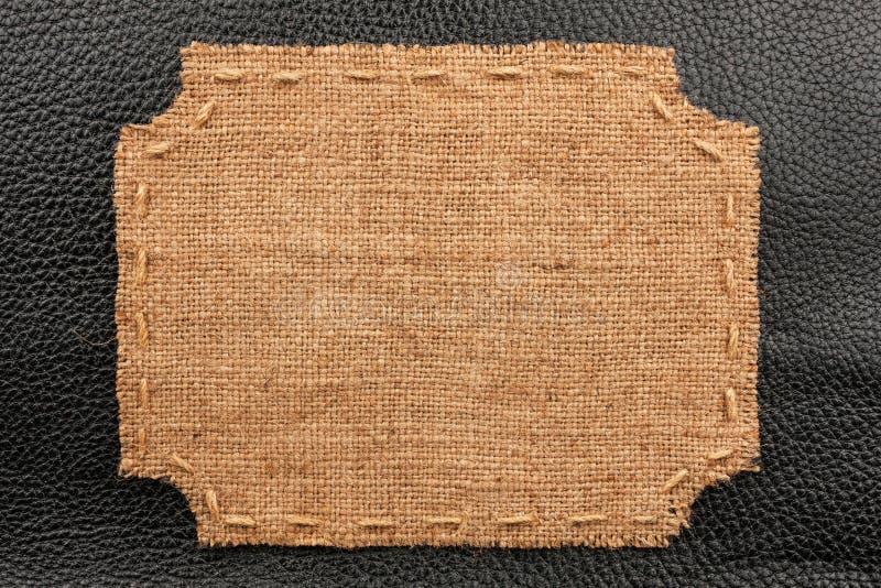 Рамка мешковины, лож на предпосылке черной кожи стоковое изображение