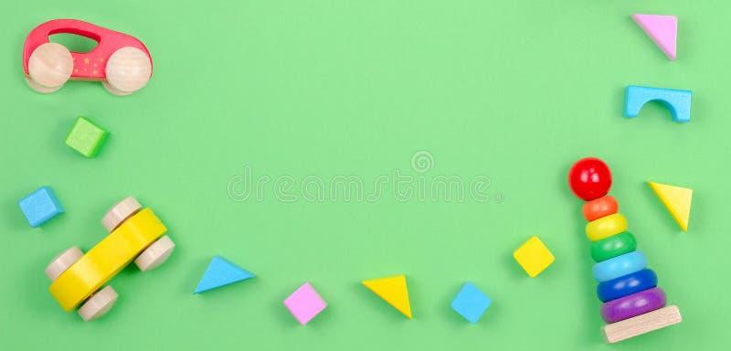 Рамка предпосылки игрушек детей с младенцем штабелируя пирамиду колец, деревянный автомобиль и красочные блоки на зеленой предпос стоковая фотография