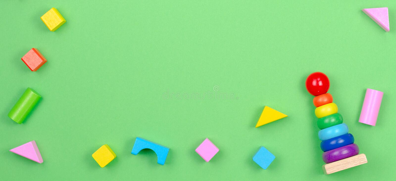 Рамка предпосылки игрушек детей с младенцем штабелируя пирамиду колец и красочные блоки на зеленой предпосылке стоковое изображение