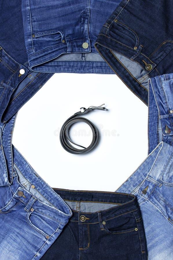 Рамка различных голубых джинсов и кожаных поясов изолированных на положении белого взгляда сверху предпосылки плоском Деталь слав стоковые фотографии rf