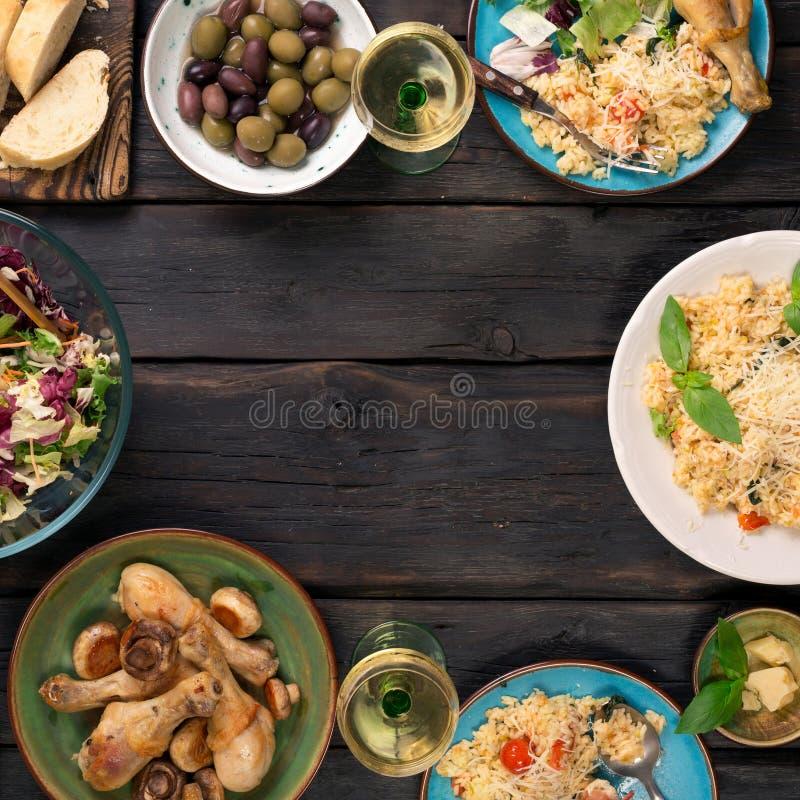 Рамка ризотто, салата, закуски, drumsticks цыпленка на деревянном стоковая фотография