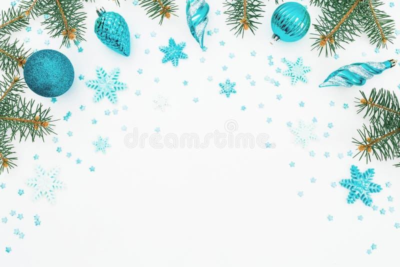 Рамка рождества ветви ели, голубого украшения и снежинки на белой предпосылке Рамка праздника Плоское положение, взгляд сверху стоковые изображения