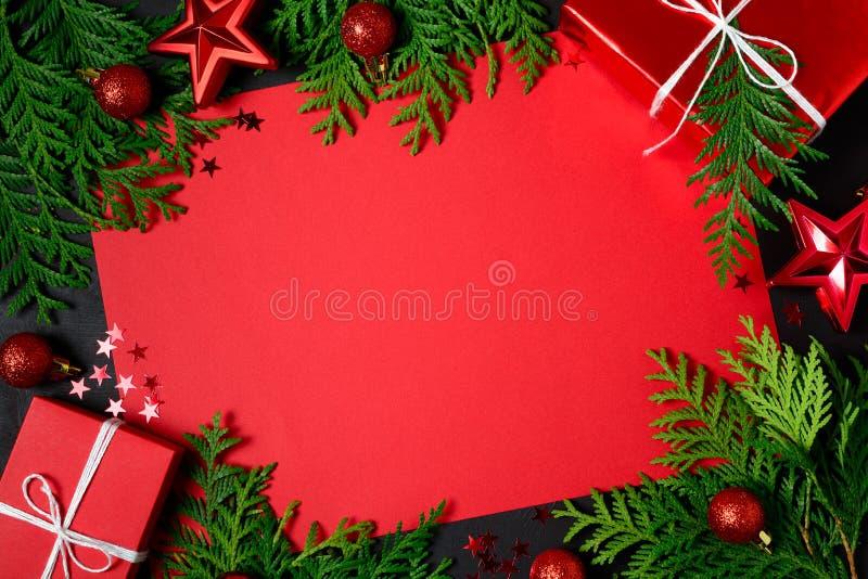 Рамка рождества красных подарочных коробок, ветвей ели, confetti, бумаги для текста и игрушек на черной предпосылке Плоское полож стоковые изображения rf