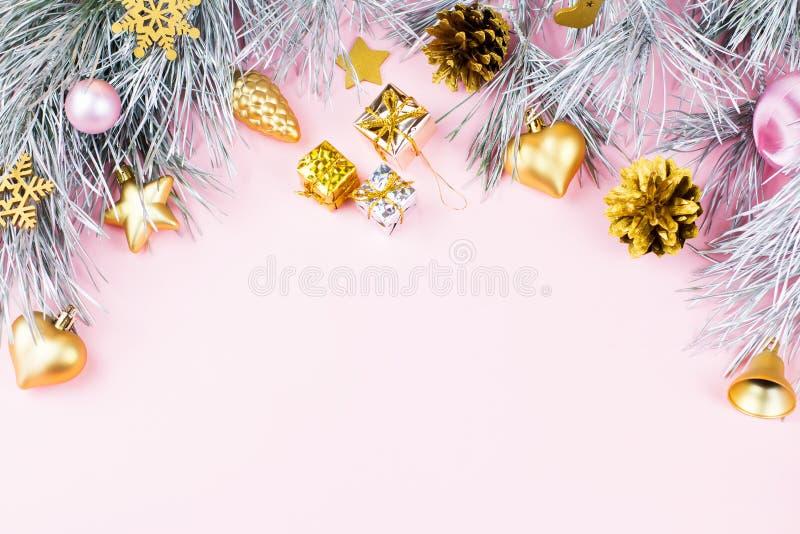 Рамка рождества с ветвями ели, конусами хвои, шариками рождества и золотыми орнаментами на предпосылке пастельного пинка стоковая фотография