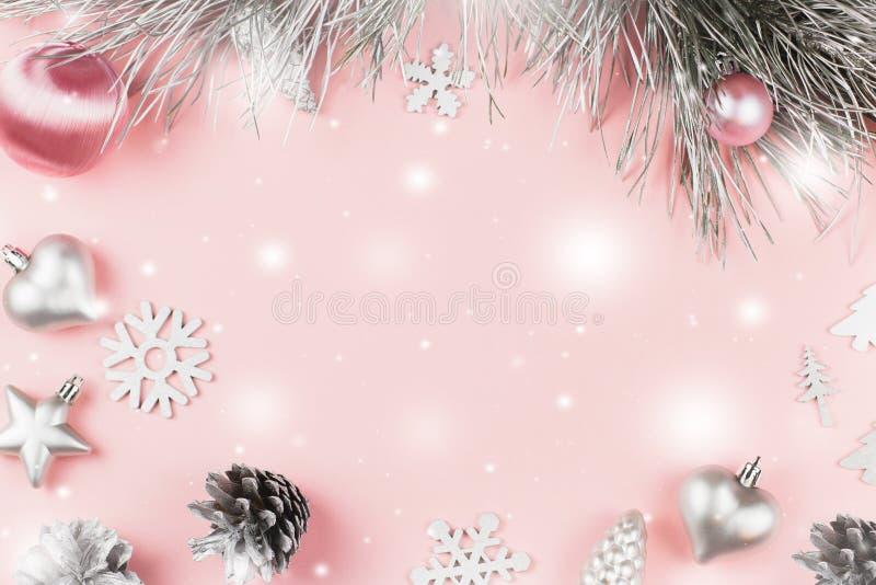 Рамка рождества с ветвями ели, конусами хвои, шариками рождества и серебряными орнаментами на предпосылке пастельного пинка стоковое изображение rf