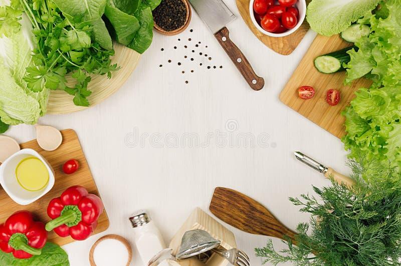 Рамка свежего зеленого салата, красной паприки, томата вишни, перца, масла и kitchenware на мягкой белой деревянной доске стоковое фото