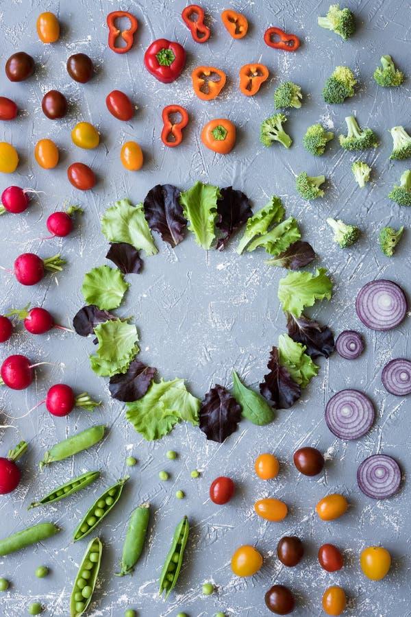 Рамка свежих органических овощей Редиска, зеленые горохи, брокколи, томат и лук на серой предпосылке, с космосом экземпляра стоковая фотография rf