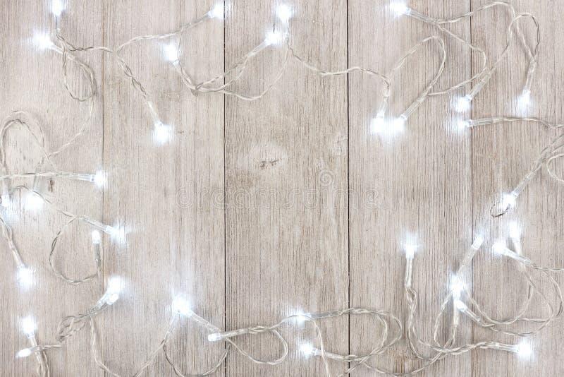 Рамка светов белого рождества над светом - серой древесиной стоковое изображение rf