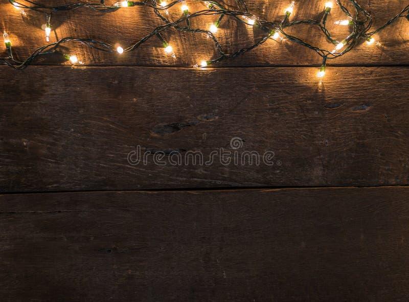 Рамка светов рождества на старой деревянной предпосылке стола и пустом космосе для текста Взгляд сверху с космосом экземпляра стоковое фото rf