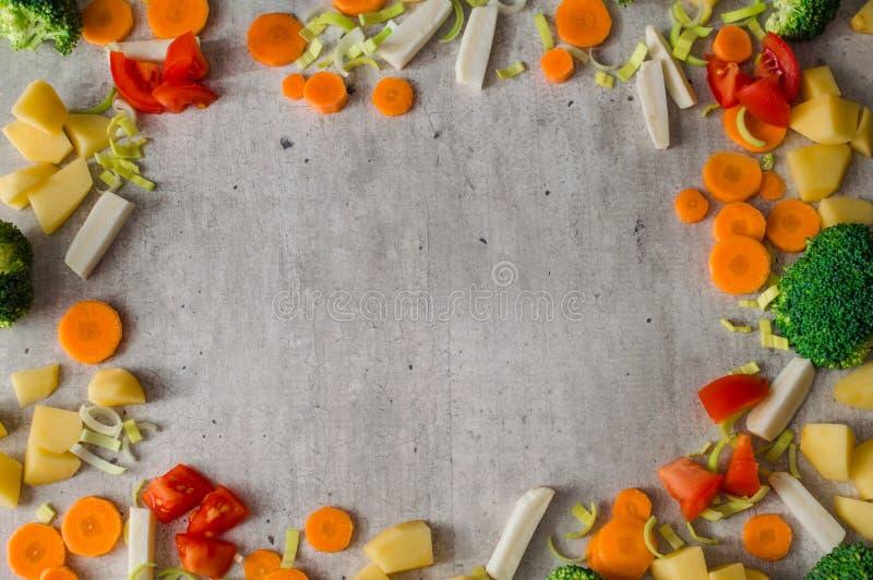 Рамка сочных отрезанных овощей на серой каменной предпосылке стоковое изображение rf