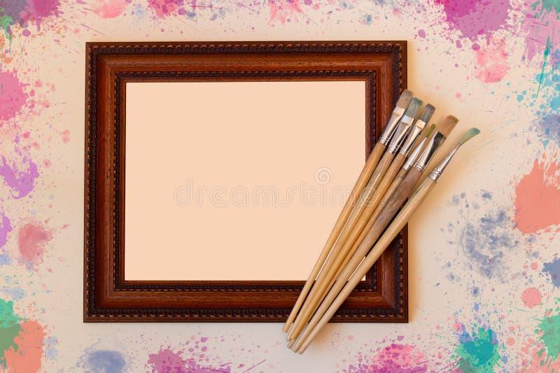 Рамка с кистями на бежевой предпосылке стоковые изображения