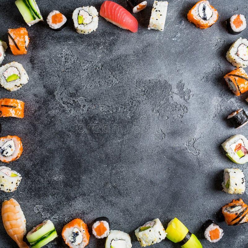 Рамка с комплектом японской еды на темной предпосылке Крены суш, nigiri, сырцовый salmon стейк, рис и авокадо Плоское положение В стоковые изображения rf