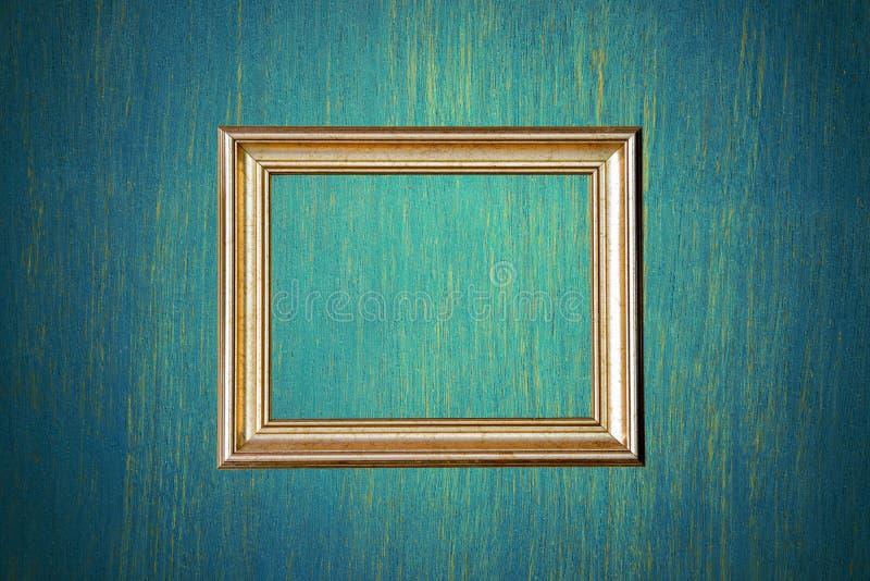Рамка фото золота на зеленой стене стоковые фото