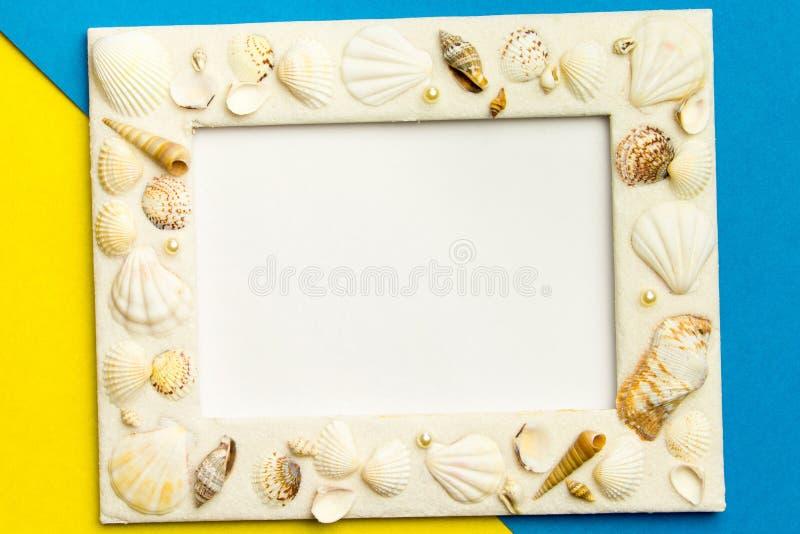 Рамка фото с раковинами на голубой и желтой предпосылке текстуры бумаги цвета стоковая фотография rf