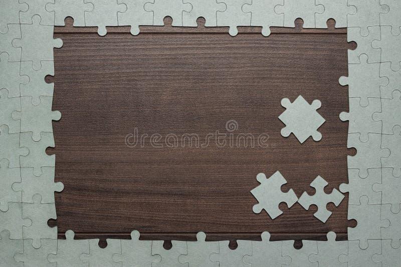 Рамка частей головоломки на деревянной предпосылке стоковое фото