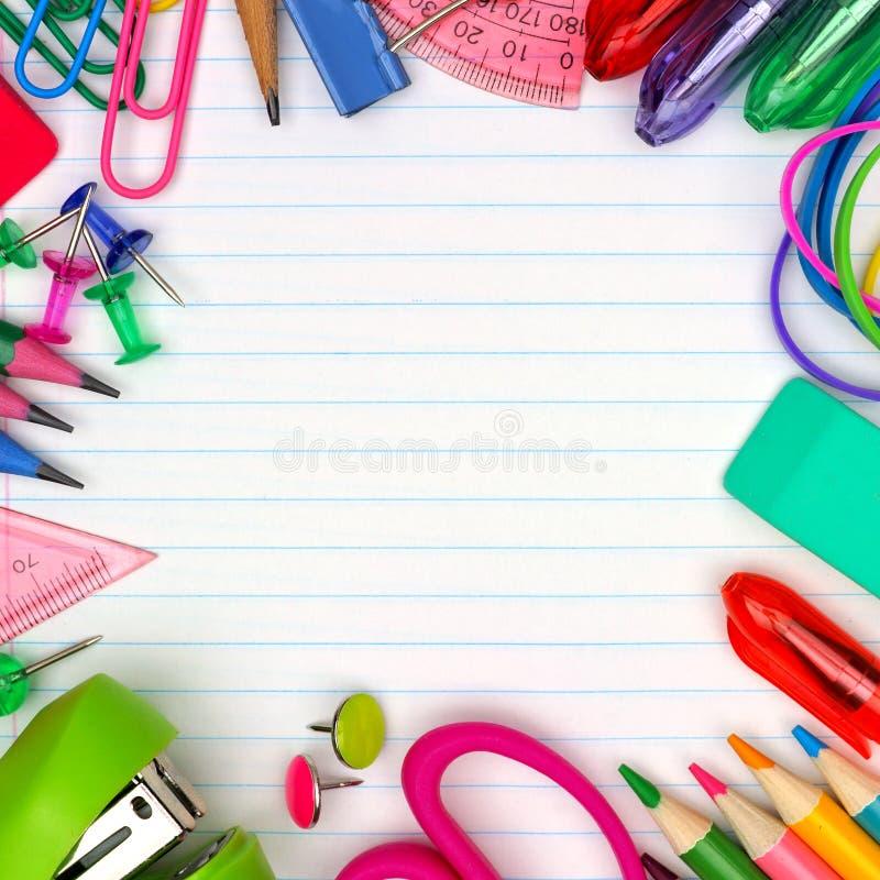 Рамка школьных принадлежностей квадратная на выровнянной бумажной предпосылке стоковые изображения