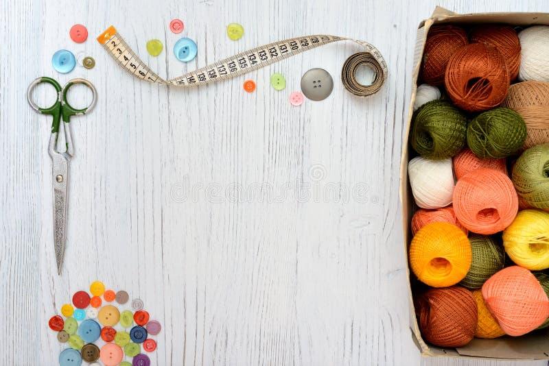 Рамка Copyspace с шить инструментами и аксессуарами на белой деревянной предпосылке стоковая фотография