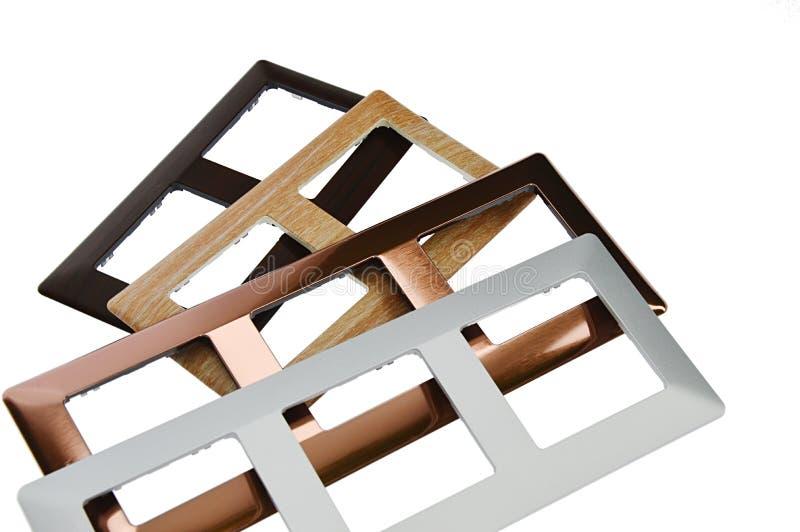 Рамки выключателя с материалами имитировать дизайна различными как древесина, медь и алюминий, белая предпосылка стоковое изображение
