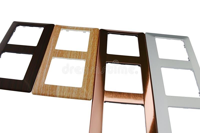 Рамки выключателя с материалами имитировать дизайна различными как древесина, медь и алюминий, белая предпосылка стоковые фото