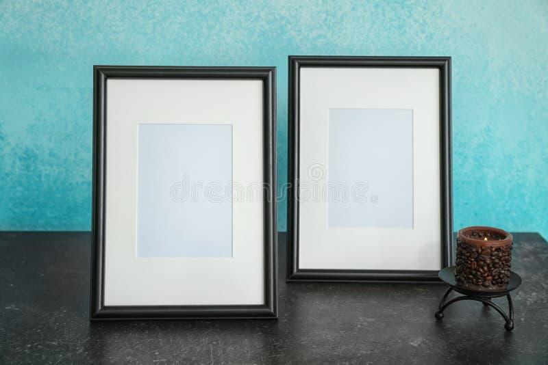 Рамки фото со свечой на таблице против предпосылки цвета стоковые изображения rf
