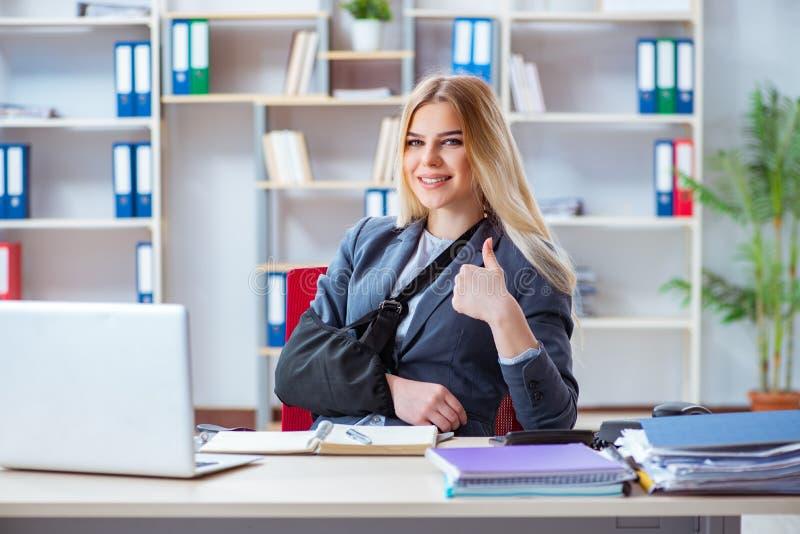 Раненый женский работник работая в офисе стоковая фотография rf