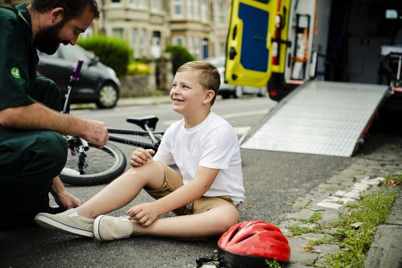 Раненый мальчик получая помощь от медсотрудников стоковое изображение