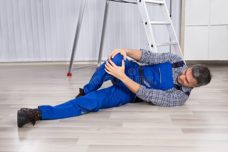 Раненый человек держа его ногу стоковое изображение rf