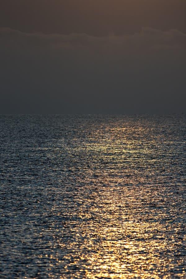 Рано утром солнечный свет отражая с морской воды штиля на море стоковые фото