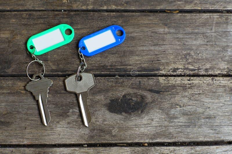 Расквартируйте ключи с кольцом для ключей бирки цвета с зеленой предпосылкой сада, концепцией свойства, космосом экземпляра стоковая фотография