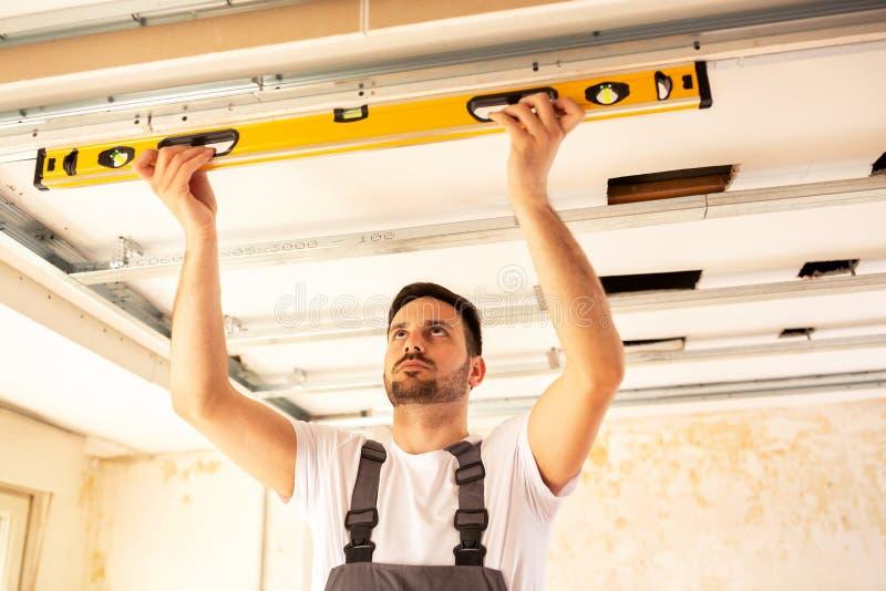 Расквартируйте работника реновации проверяя выравнивание потолка стоковое изображение rf