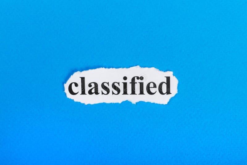 расклассифицированный текст на бумаге Слово расклассифицированное на сорванной бумаге текст остальных изображения figurine принци стоковая фотография rf