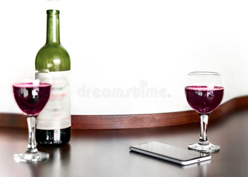 Раскройте бутылку и 2 стекла вина и мобильного телефона красной виноградины на коричневом деревянном столе и запачканной белизной стоковые фото