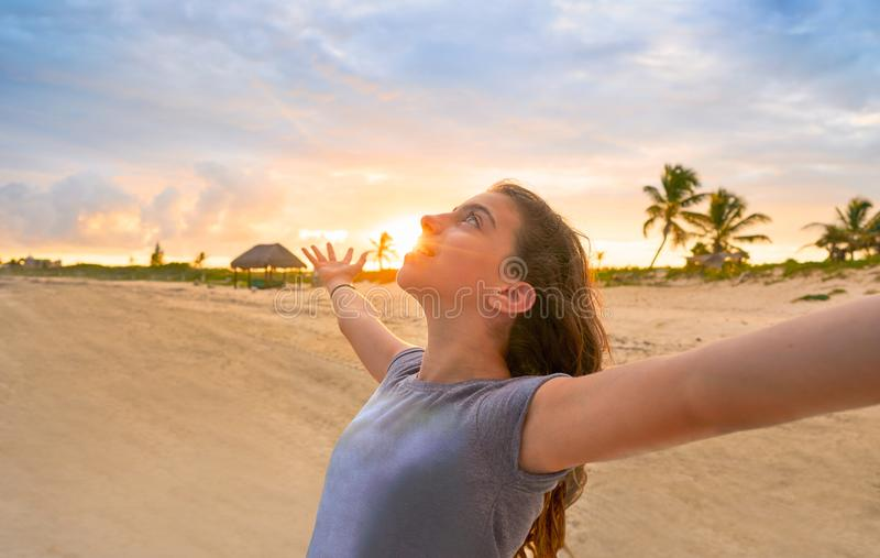 Раскройте девушку оружий на пляже Вест-Инди захода солнца стоковая фотография