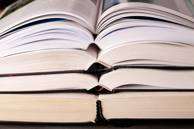 Раскройте книги штабелированные на таблице стоковые изображения rf